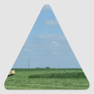 a tractor cutting wheat fields and a water tower triangle sticker