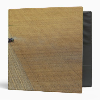 A tractor harvesting 3 ring binder