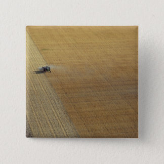 A tractor harvesting pinback button