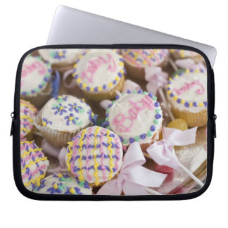 A tray of baby rattle cupcakes at a baby shower. laptop computer sleeves