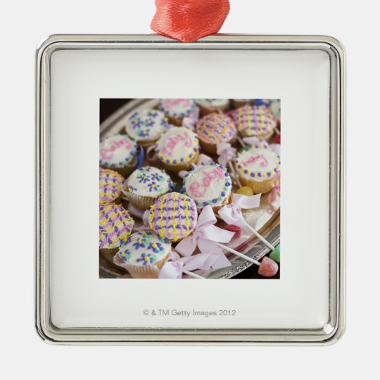 A tray of baby rattle cupcakes at a baby shower. metal ornament