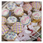 A tray of baby rattle cupcakes at a baby shower. ceramic tile
