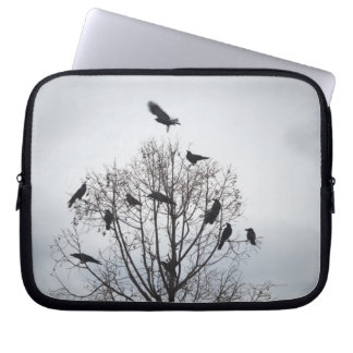 A tree in which many crows have rest laptop computer sleeve