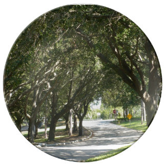 A tree lined street on a porcelain plate. porcelain plate