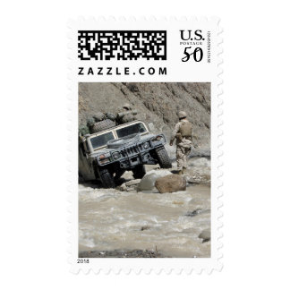 A US Marine guiding the driver of a Humvee Postage