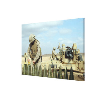 A US Marine prepares howitzer rounds to be fire Stretched Canvas Prints
