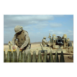 A US Marine prepares howitzer rounds to be fire Poster