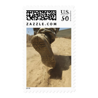 A US soldier walks along a dirt path Postage