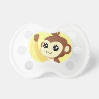 A very cute and kawaii monkey holding a banana pacifier