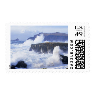 a view of the waves crashing against rocks stamp