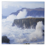 a view of the waves crashing against rocks large square tile