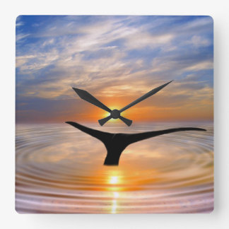 A whales tail at sunset square wall clock