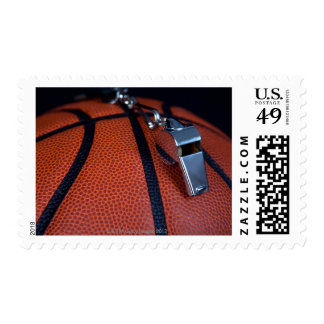 A whistle rests on top of a basketball postage stamp