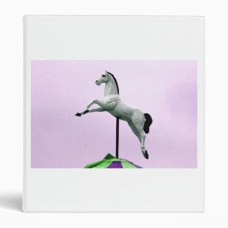 A white horse carousel statue against purple binder