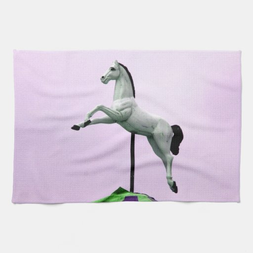 A white horse carousel statue against purple kitchen towels