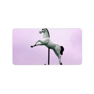 A white horse carousel statue against purple custom address label