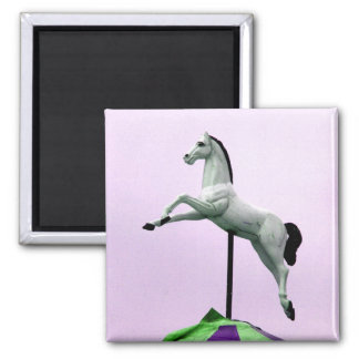 A white horse carousel statue against purple magnets