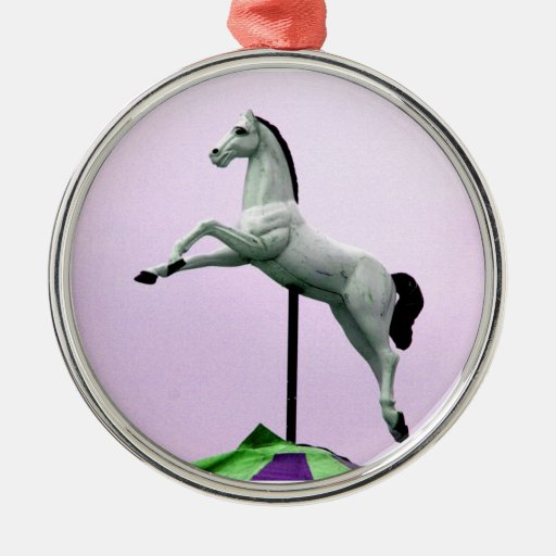 A white horse carousel statue against purple christmas tree ornament
