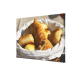 A wicker breakfast basket with croissants, and canvas print