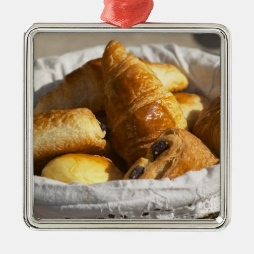 A wicker breakfast basket with croissants, and metal ornament