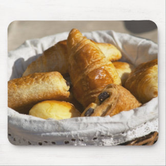 A wicker breakfast basket with croissants, and mouse pad