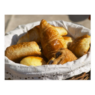 A wicker breakfast basket with croissants, and postcard