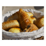 A wicker breakfast basket with croissants, and poster