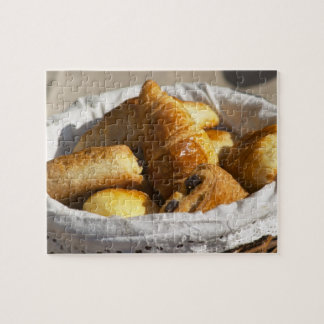 A wicker breakfast basket with croissants, and puzzle