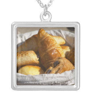 A wicker breakfast basket with croissants, and silver plated necklace
