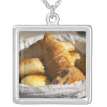 A wicker breakfast basket with croissants, and square pendant necklace