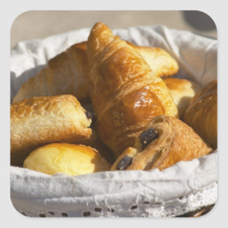 A wicker breakfast basket with croissants, and square sticker