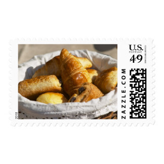 A wicker breakfast basket with croissants, and stamp