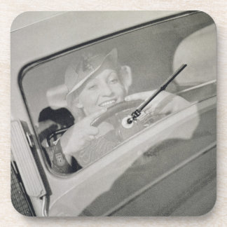 A woman driving, c.1930s (photogravure) drink coaster