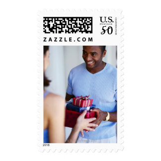 a woman gifting a young man postage