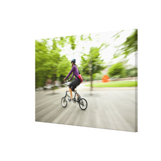 A woman using a folding bike to commute canvas print