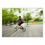 A woman using a folding bike to commute card