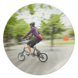 A woman using a folding bike to commute dinner plate
