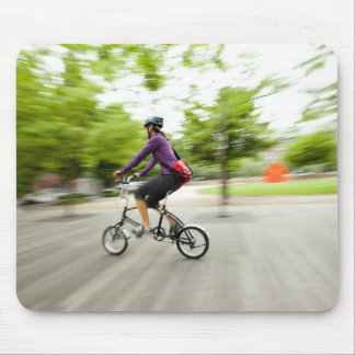 A woman using a folding bike to commute mouse pad