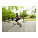 A woman using a folding bike to commute postcard