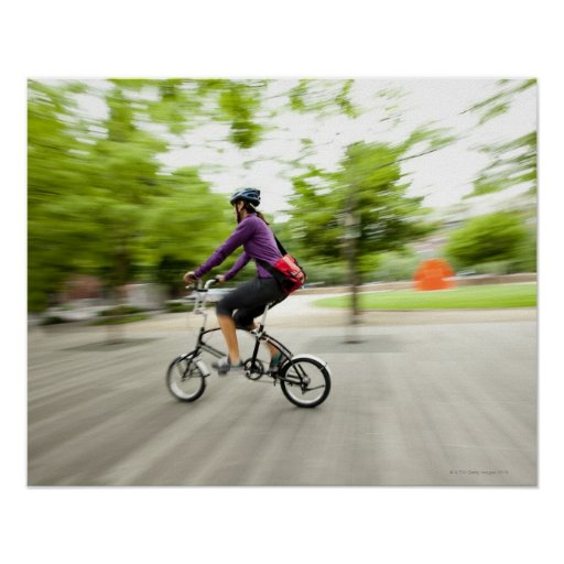 A woman using a folding bike to commute poster
