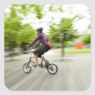 A woman using a folding bike to commute square sticker
