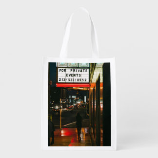 A woman walks in the city reusable grocery bag