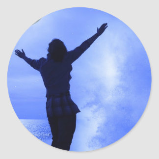 a woman with raised hands facing a wave and full m classic round sticker