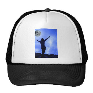 a woman with raised hands facing a wave and full m trucker hat