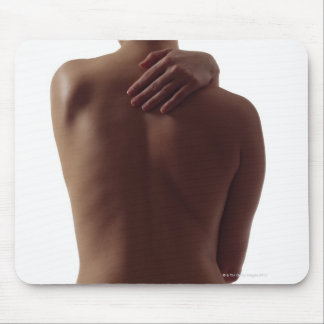 A woman's bare back with one hand reaching mouse pad