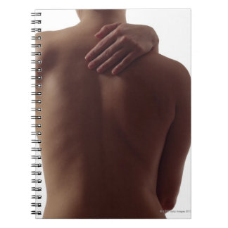 A woman's bare back with one hand reaching notebook