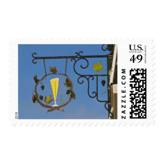 A wrought iron sign that illustrates the theme postage