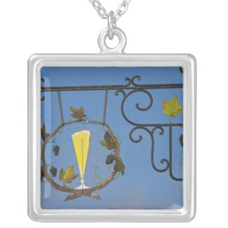 A wrought iron sign that illustrates the theme square pendant necklace