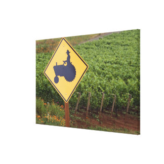 A yellow tractor crossing sign in the vineyard