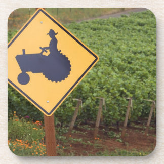 A yellow tractor crossing sign in the vineyard drink coaster